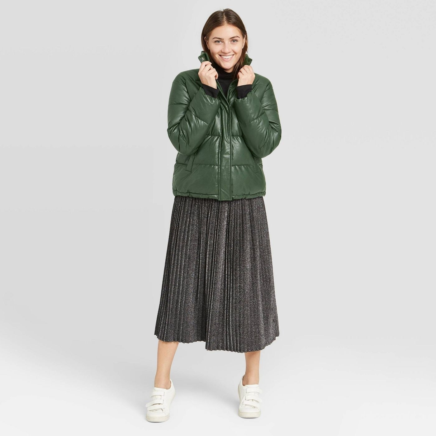 Model in green puffer jacket and metallic skirt