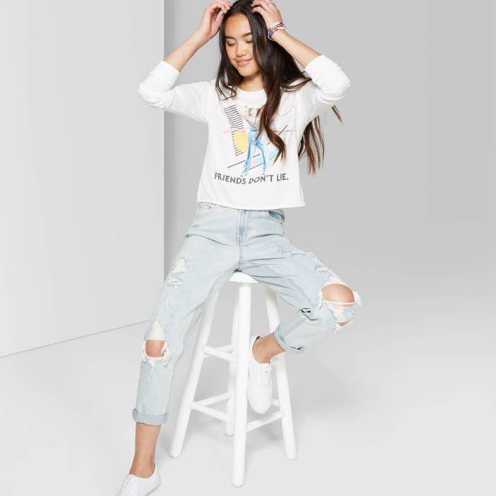 Model in distressed mom-jeans and sweatshirt