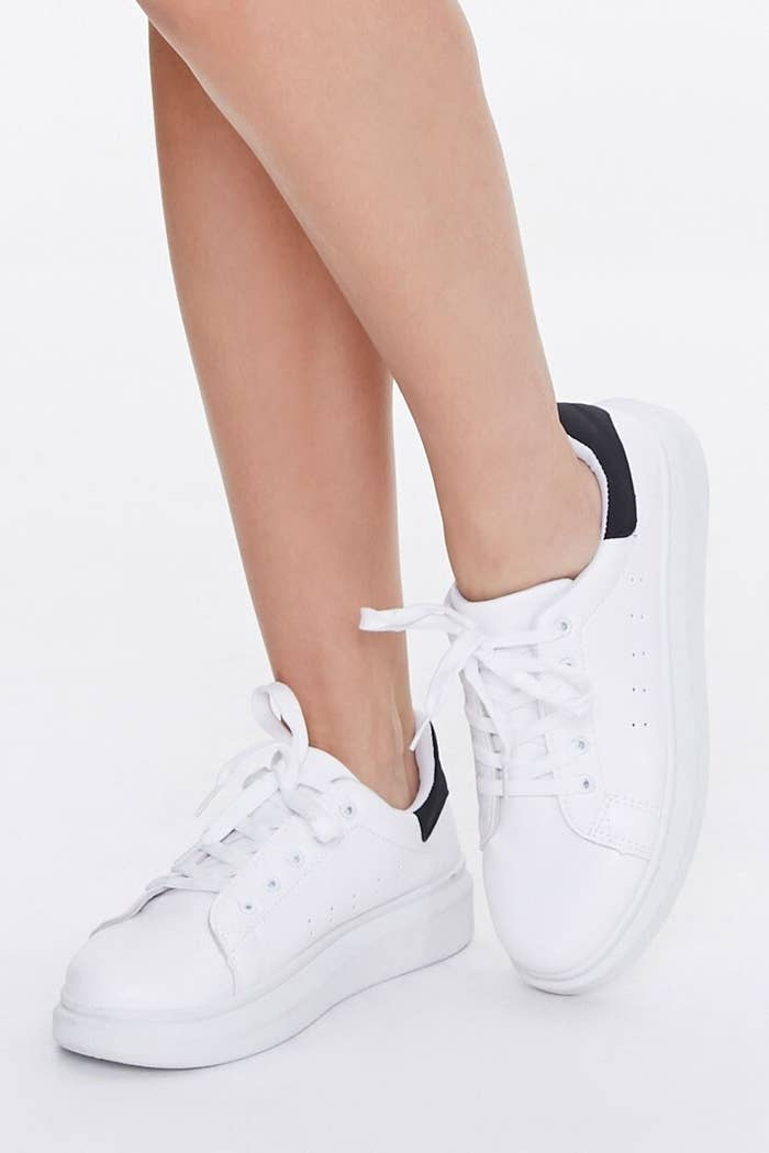 The white lace-up sneakers with thick platform sole and black coloring on the heels