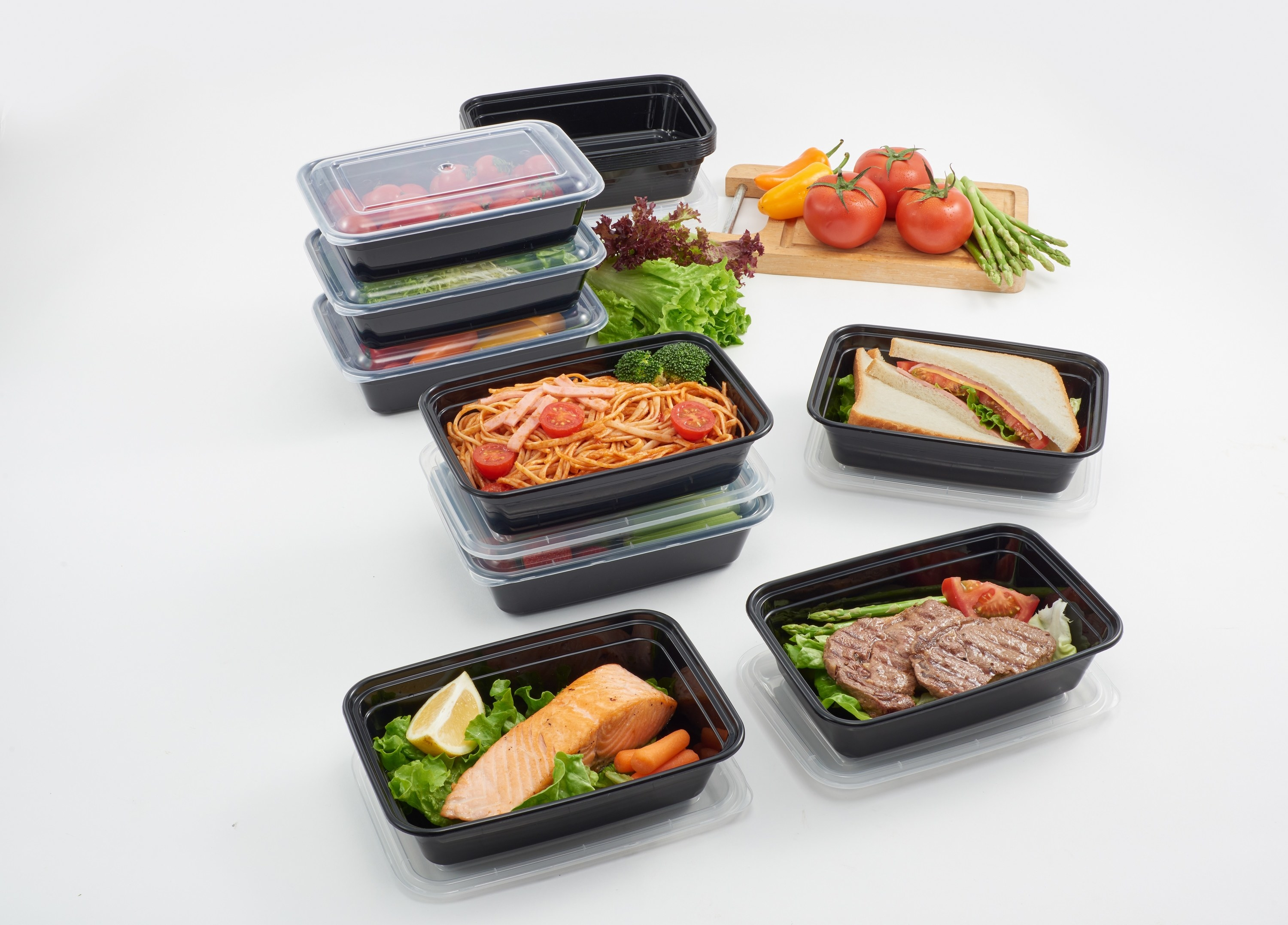 black meal prep containers holding spaghetti, salmon, beef, sandwiches etc