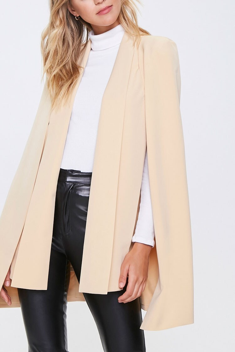 Model wearing the blazer with cape-style open sleeves and an open front in beige