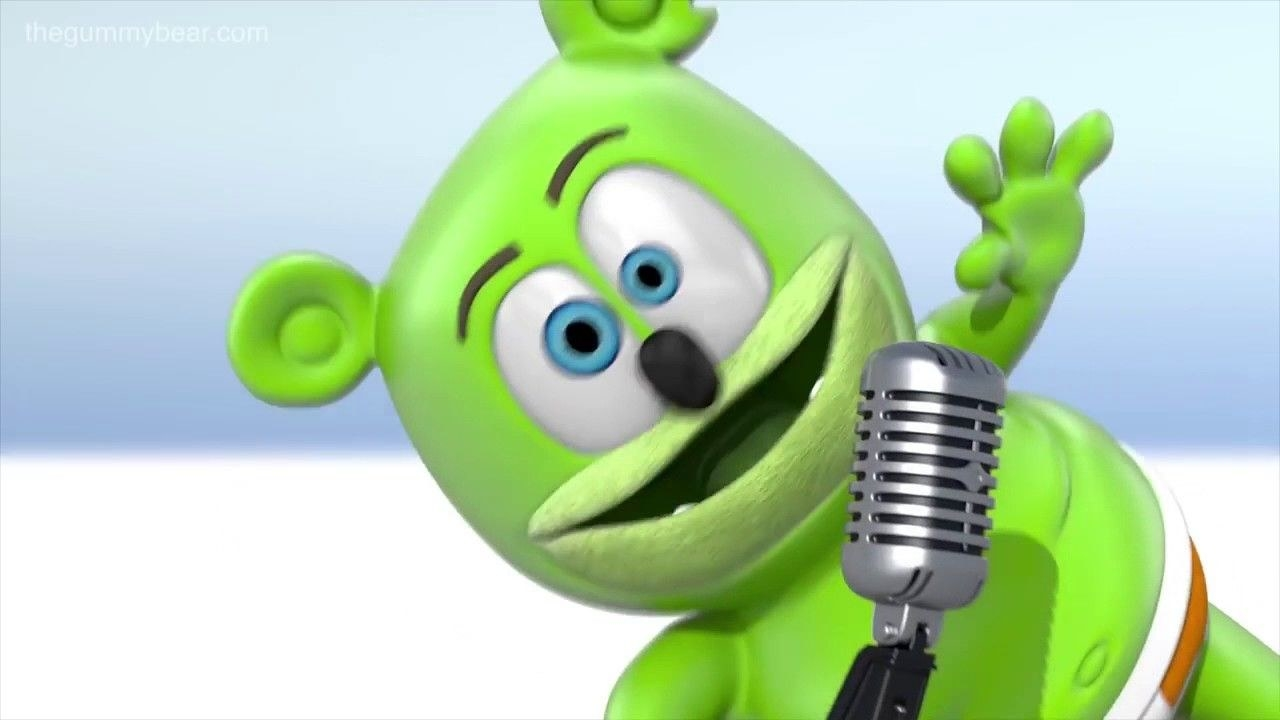 A green living gummy bear singing into a retro microphone