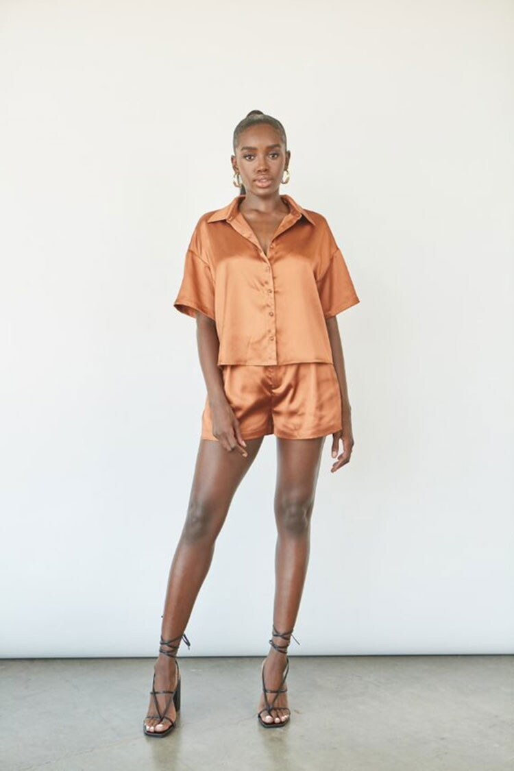 Model wearing the button-front collared short-sleeved shirt and high-rise shorts with pockets in a satin brown fabric