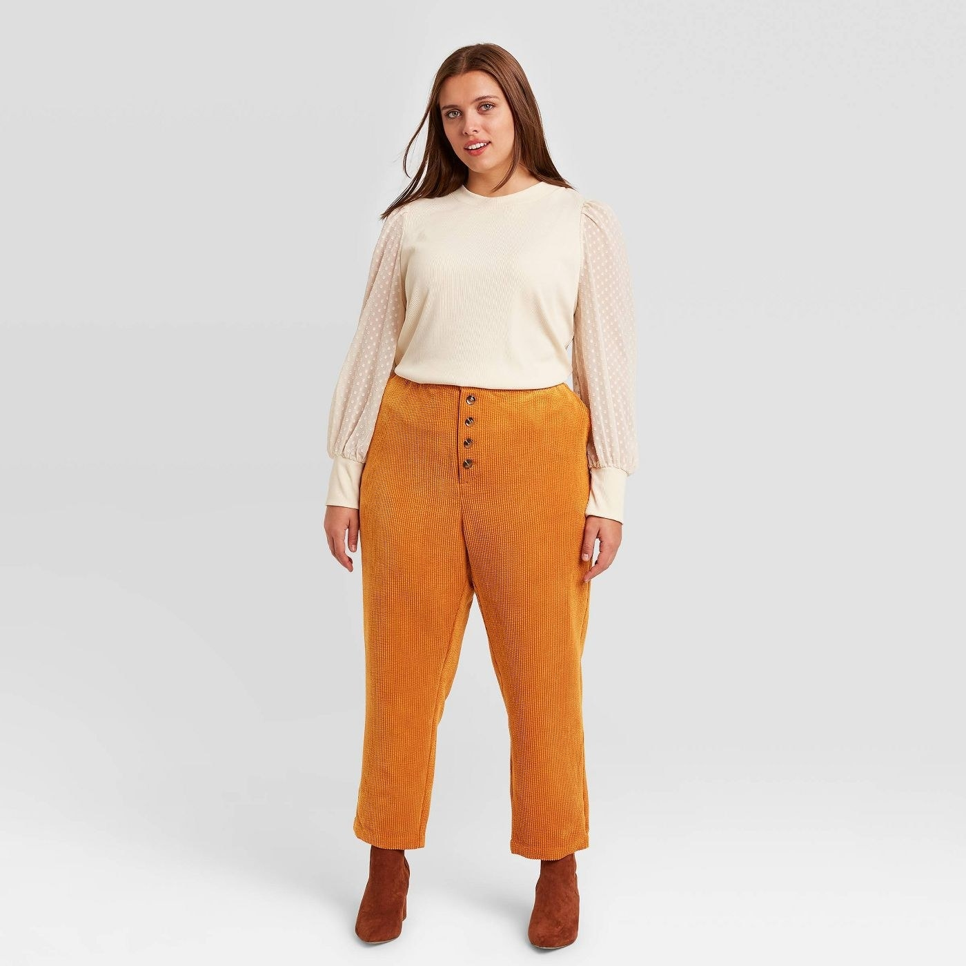 Model in orange corduroy pants and white blouse