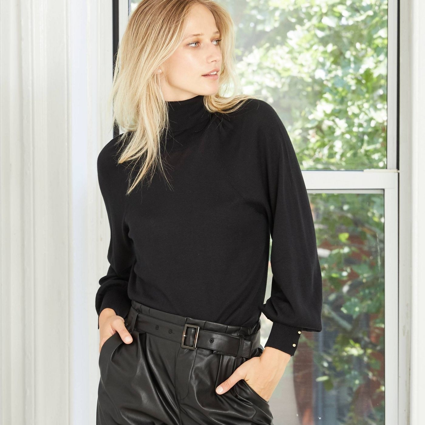 Model in black turtleneck with puffy sleeves