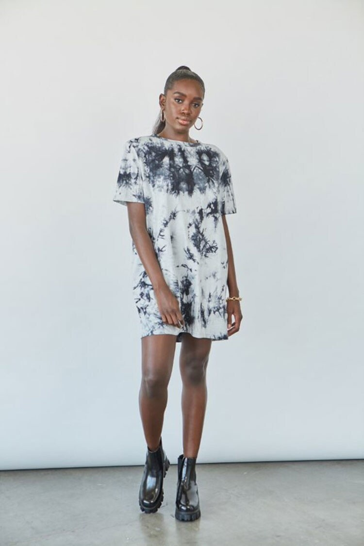 Model wearing the short-sleeved t-shirt dress with crew neck and shoulder pads and black tie-dye wash