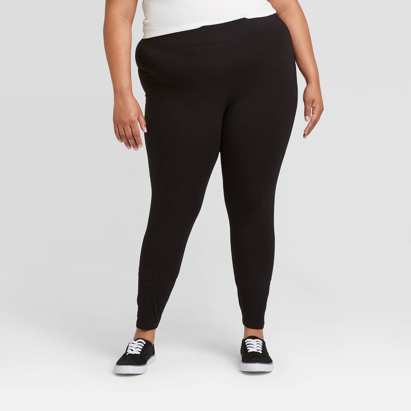 Model in high-waisted black leggings