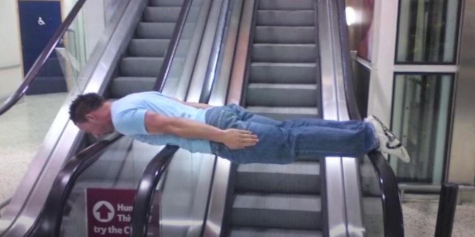A man planking on an escalator