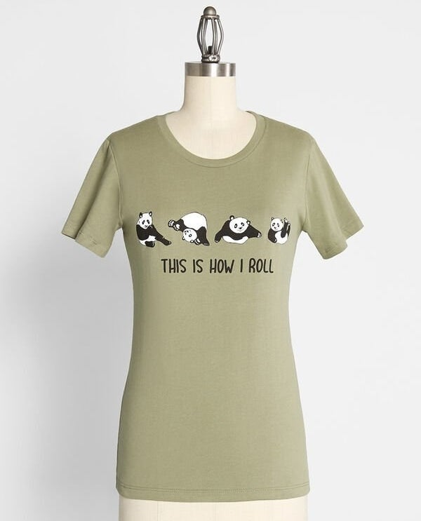 "The light green tee with the text ""this is how I roll"" printed on it and four different graphics of a panda rolling around printed on it"