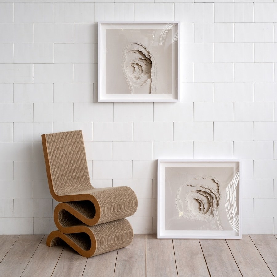 Framed wall art that looks like several pieces of thick paper ripped into a hole
