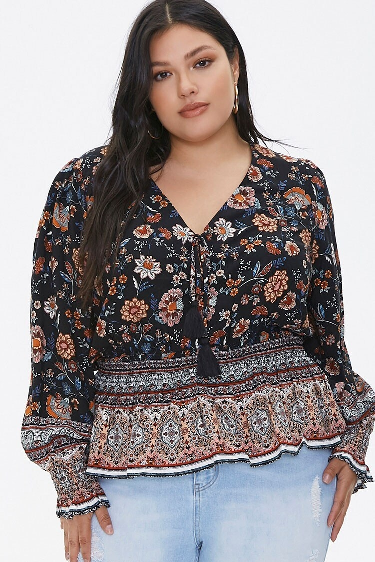 The woven tunic with a v-neck, button-down front, elastic around the waist with a flared hem, and bell sleeves in a black, white, and tan floral pattern