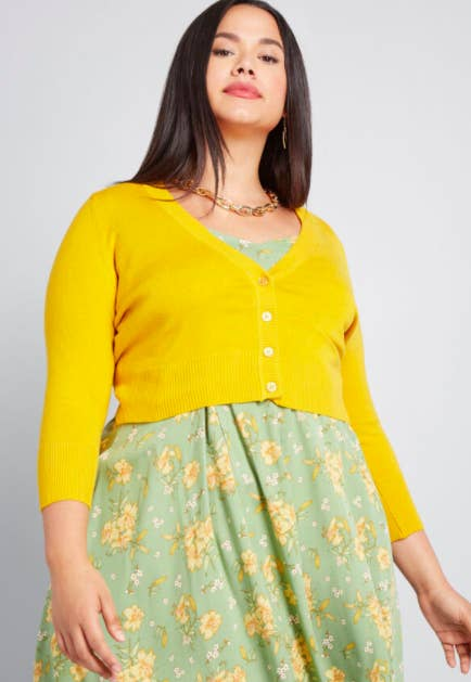 Model wears bright yellow cropped cardigan with gold link necklace and green and yellow floral A-line dress