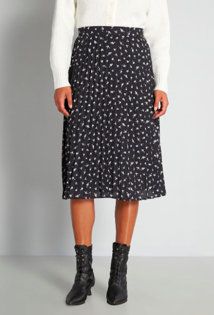 Model wears black floral midi skirt with a white cropped cardigan and black Victorian-inspired booties