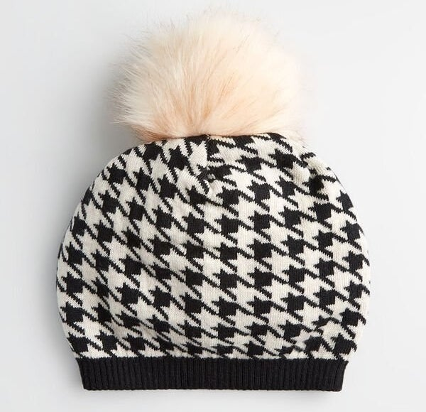 The black and white patterned hat with the cream-colored pom pom on top of it