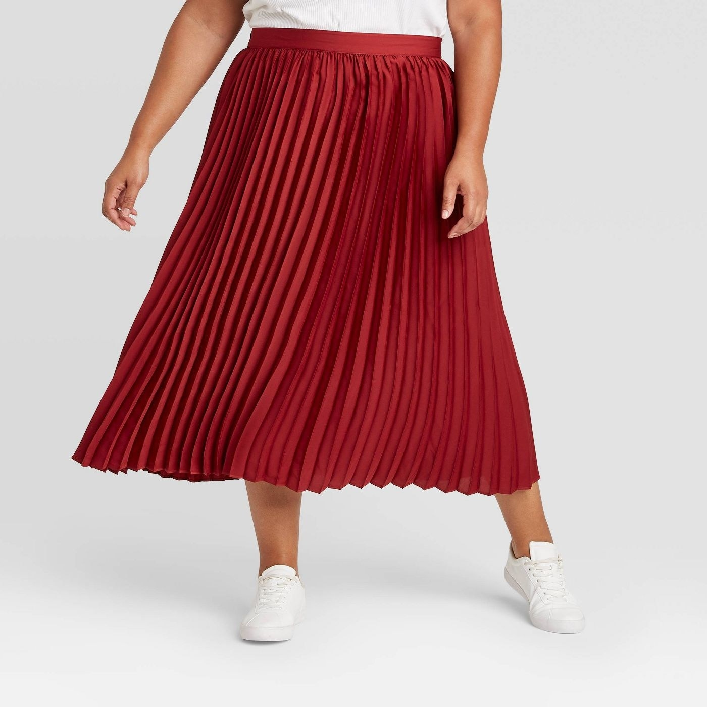 Model in red pleated skirt and white sneakers