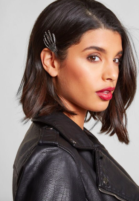 Model wears skeleton hand hair clip in their lob-styled hair