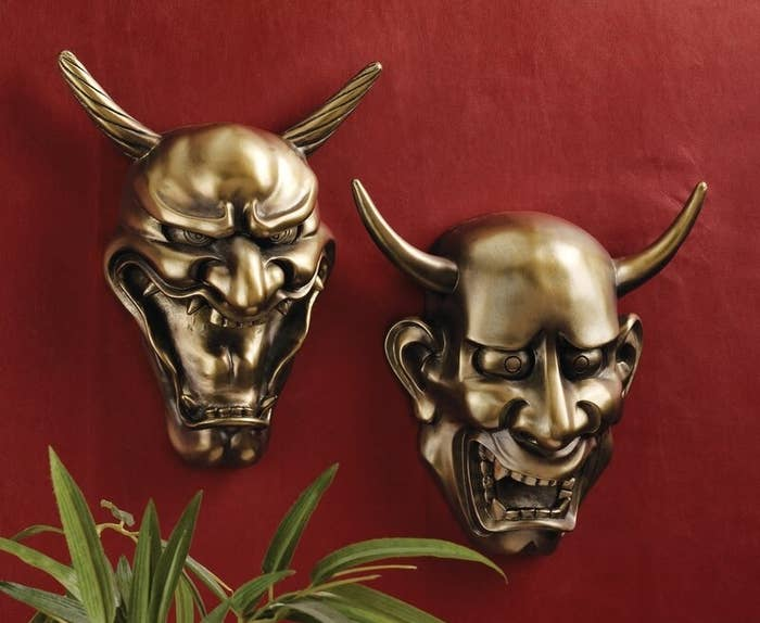 The twin masks hung side by side on a red wall