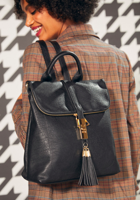 Model wears a strappy black backpack with a zip-up front and tassel detailing on their back
