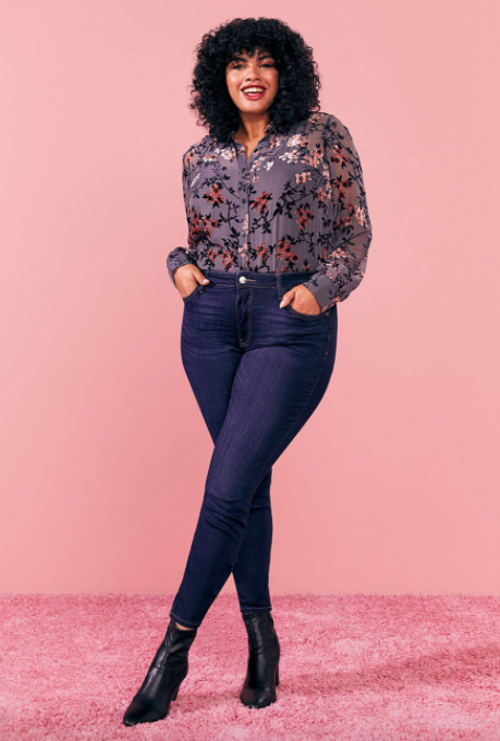 Model wears dark blue skinny jeans with a purple floral blouse and pointed black booties