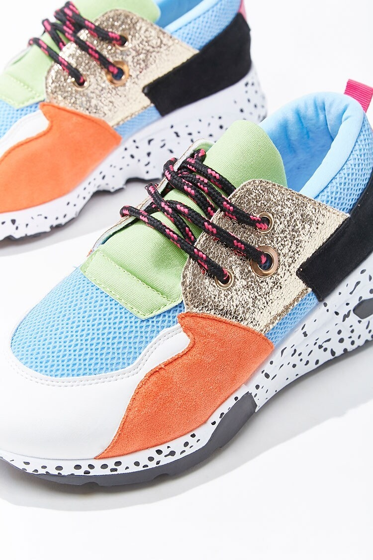 Low-top sneakers with an orange, blue, and green color block design with mesh, faux suede, metallic panels, and a white sole with black speckles