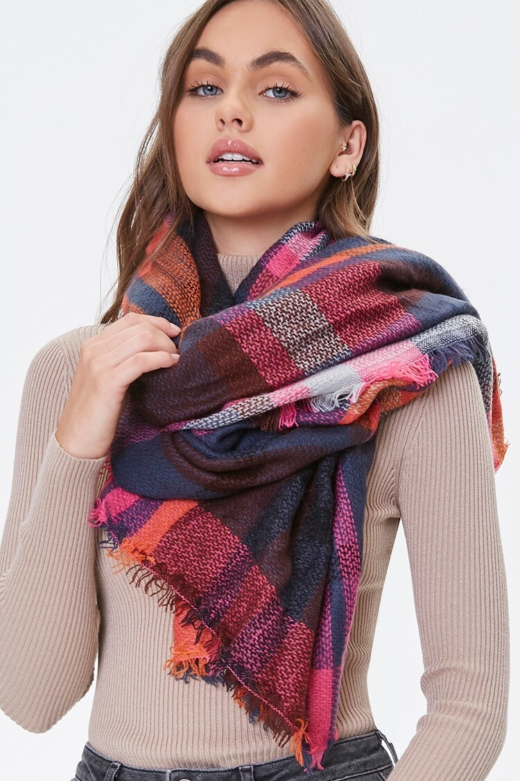 Model wearing the pink, red, orange, and purple plaid-print scarf draped around their neck