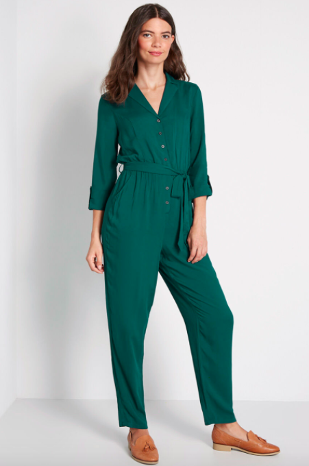 Model wears jade green long-sleeve jumpsuit with tan suede loafers