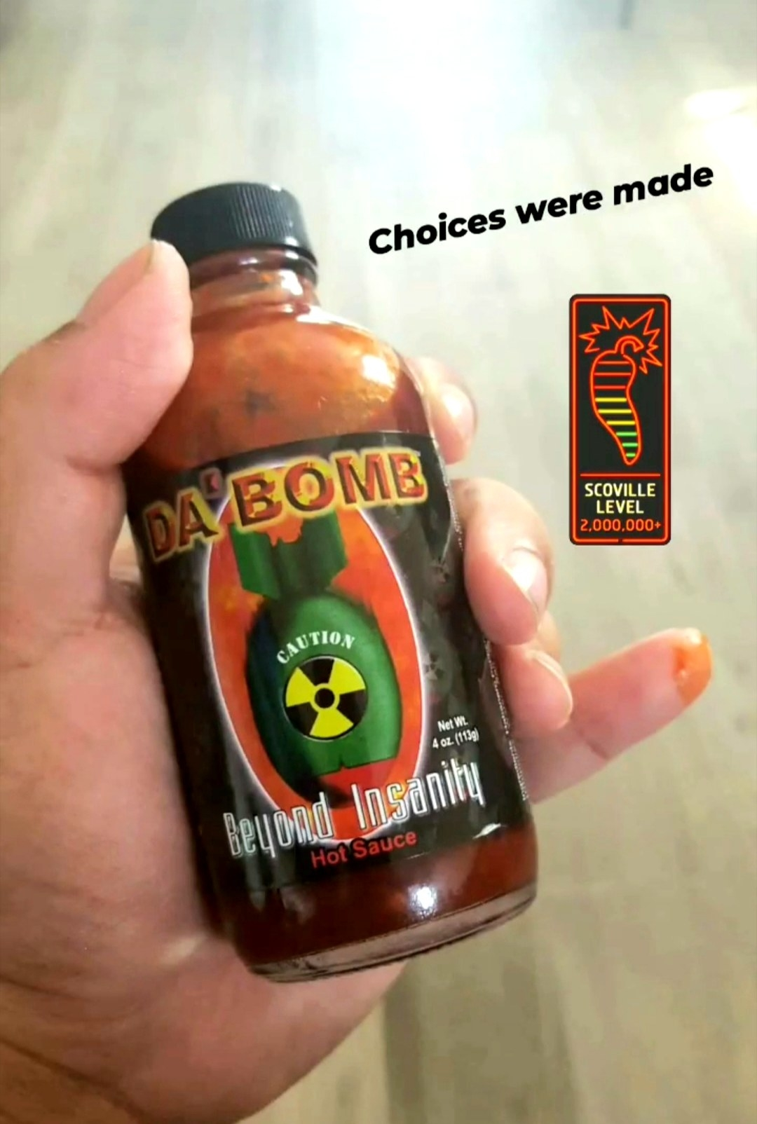 Sarah holding a bottle of Da Bomb Beyond Insanity hot sauce, the photo has the caption that says Choices were made