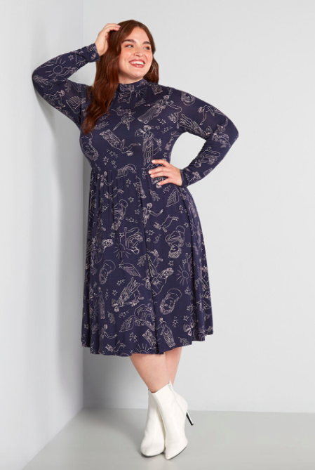 Model wears navy a-line dress with Greek mythology print and white booties