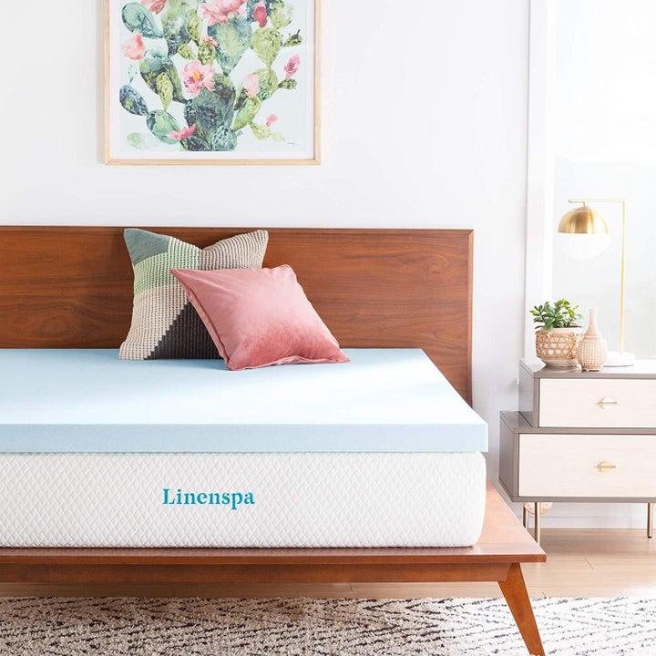 blue two-inch memory foam topper on a mattress