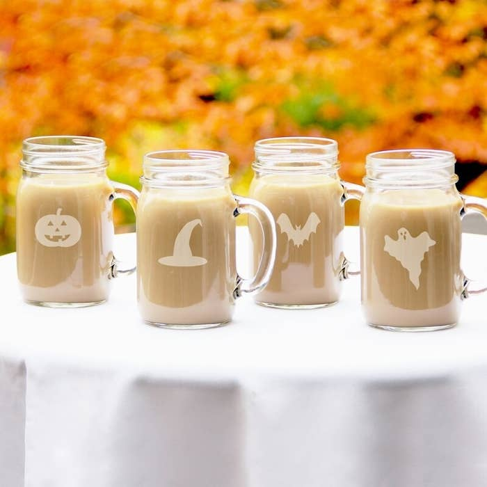 Four of the mason jars filled with coffee in a fall landscape