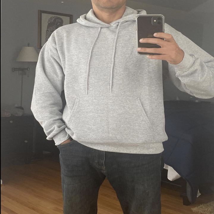 Reviewer in a gray hoodie with a front pocket and drawstrings at the collar