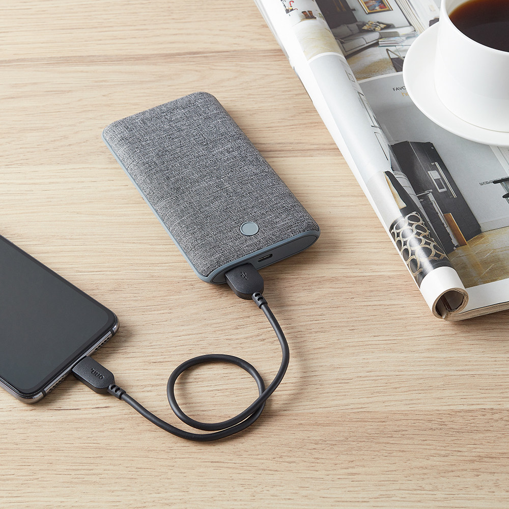 phone plugged into a gray portable battery pack on a desk