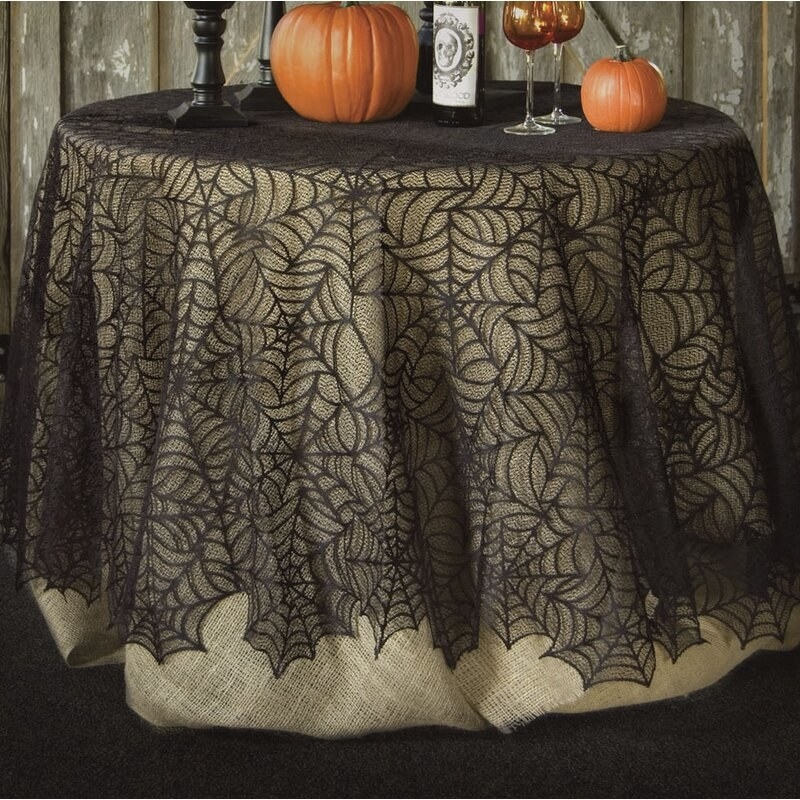 The table cloth featured on top of a burlap table cloth to show the spiderweb design