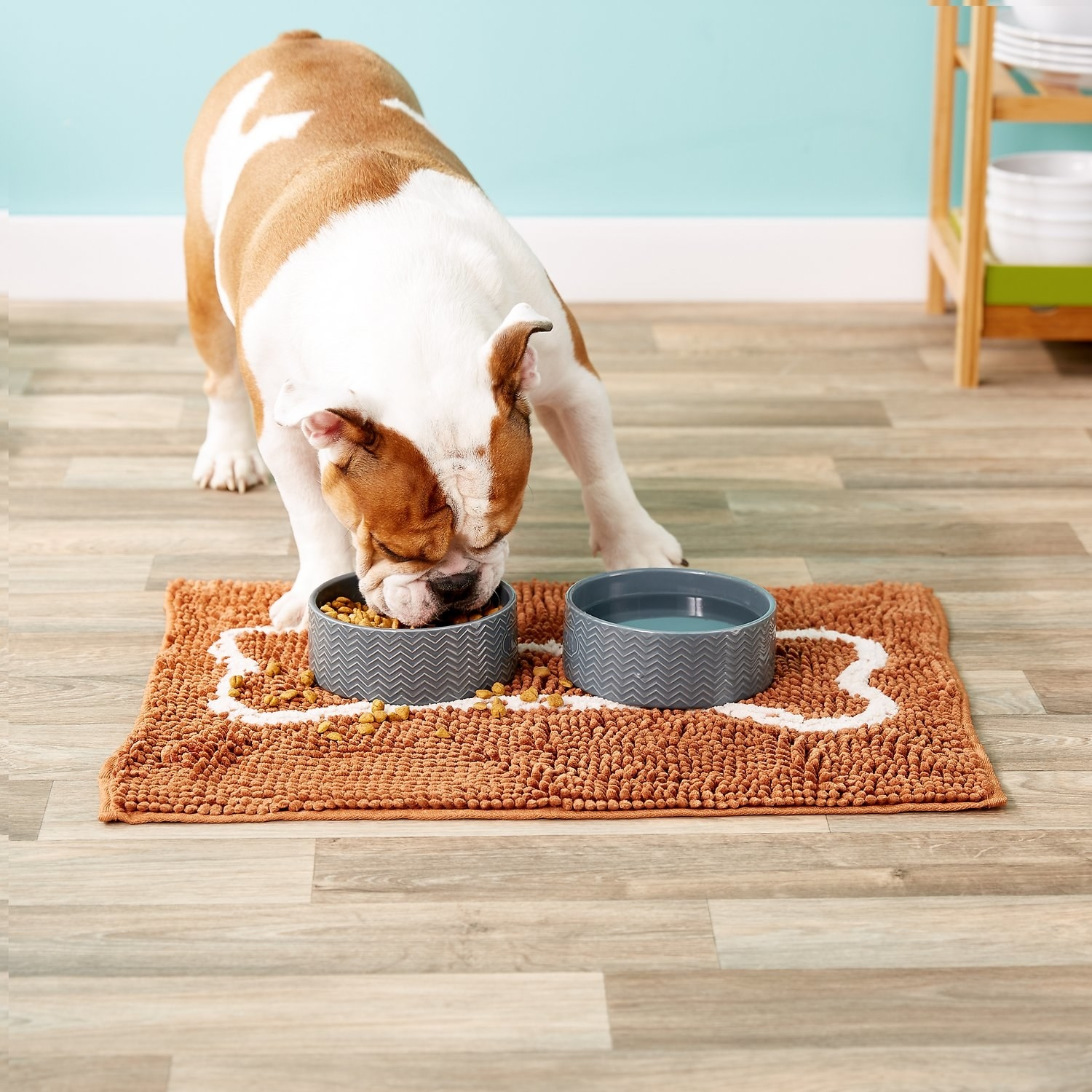 A dog eats from a bowl placed on top of the caramel brown Soggy Doggy Slopmat Microfiber Placemat
