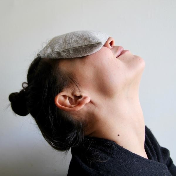 A person tilts their head back with an eye pillow resting over their eyes