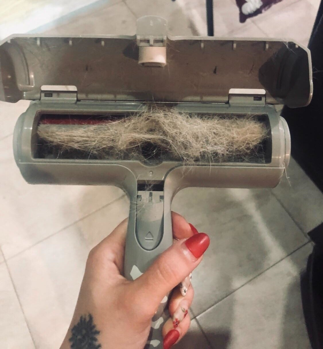 reviewer showing all of the pet hair in their roller