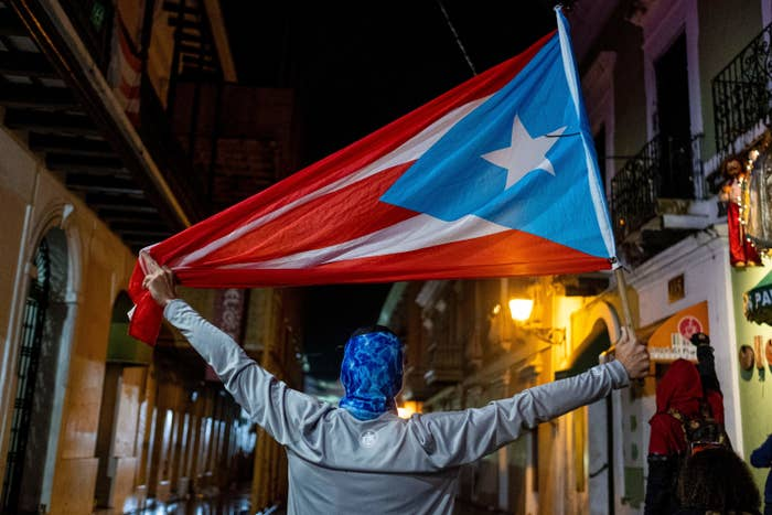 A protester holds a Puerto Rican flag
