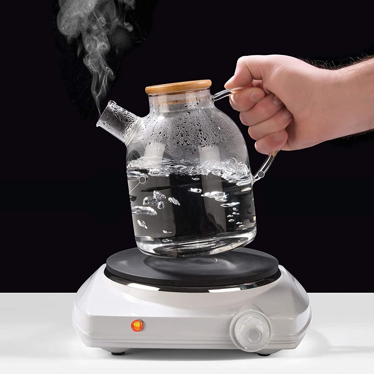 A person lifts the boiling kettle off a hot plate