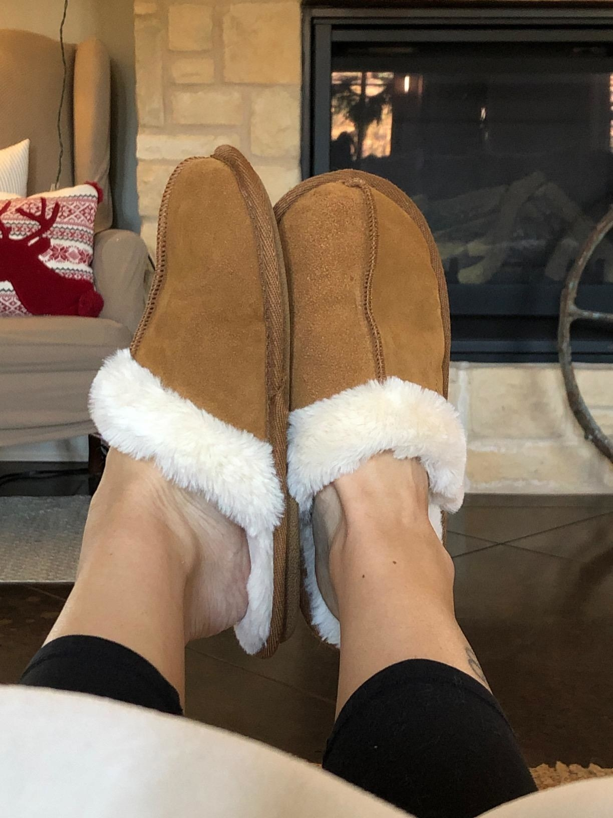 A reviewer wearing the brown slippers which are lined with fur