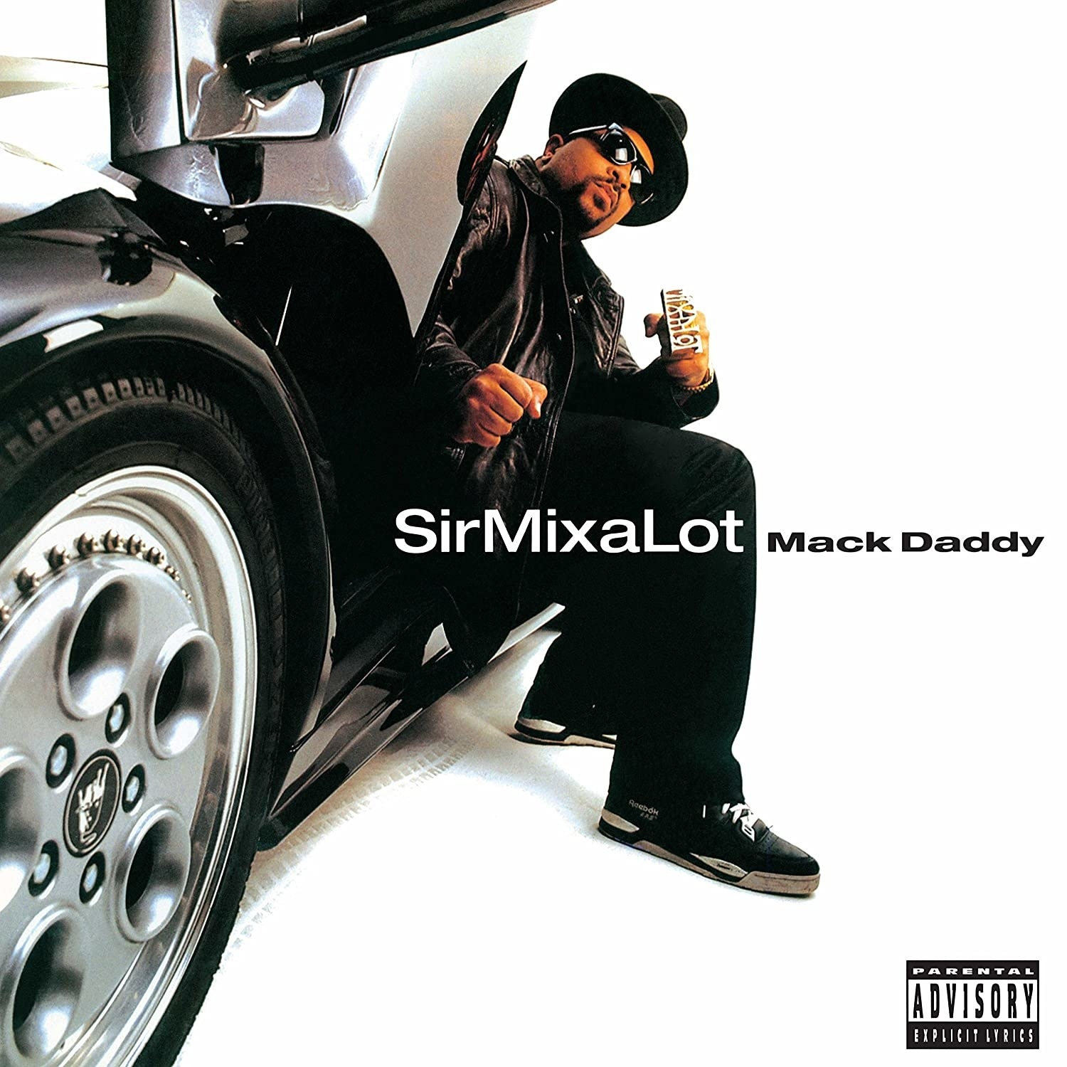 album cover of Mack Daddy showing Sir Mix-a-Lot sitting with his legs out of the seat of a gull-winged car