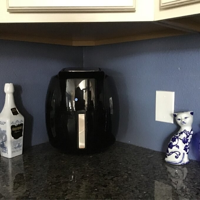 A black air fryer on a kitchen countertop