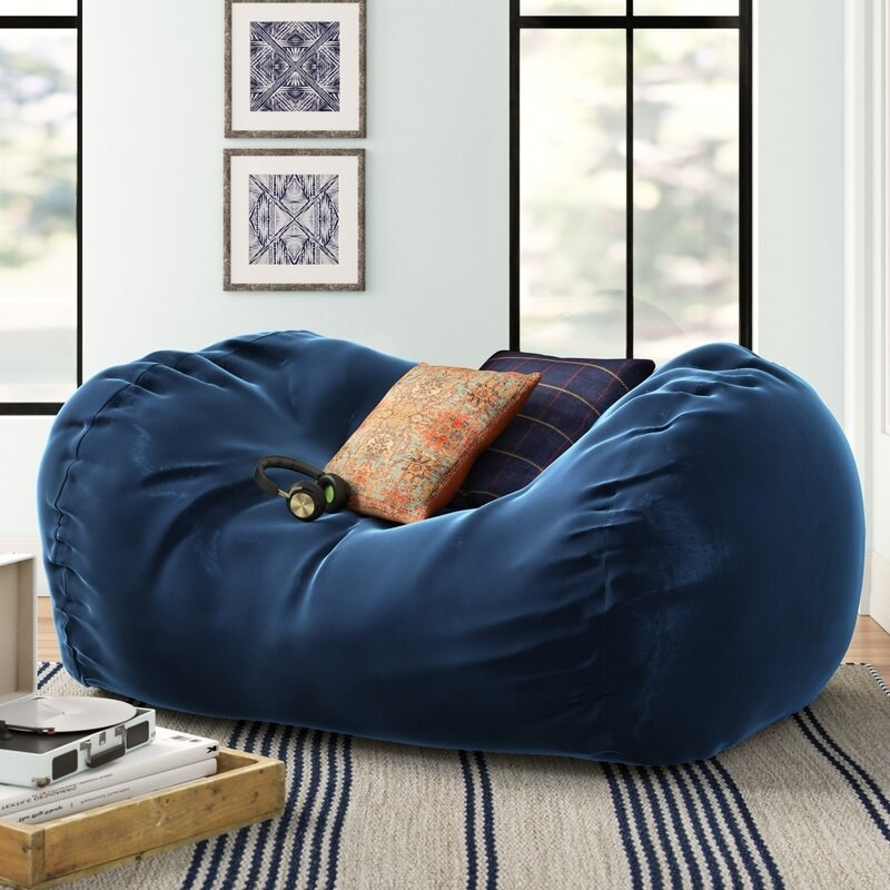 a navy bean bag chair with two pillows and headphones sitting on top