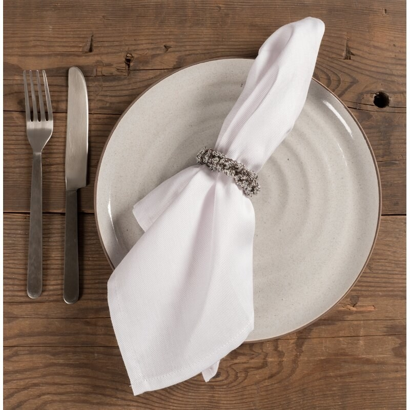 A white napkin in a napkin ring on a place setting