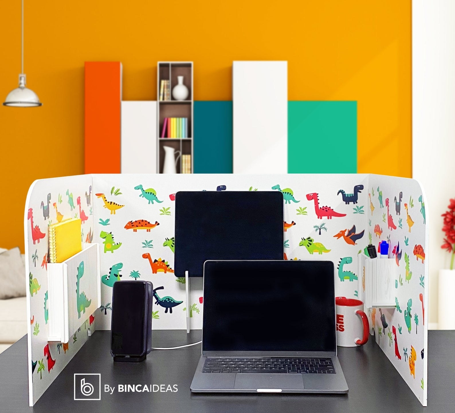 a three-side wooden stand that has two walls and a back (like a box with a missing side). It has a dinosaur print and is standing up on a table. The empty space in the middle has a laptop, speaker, and mug sitting there