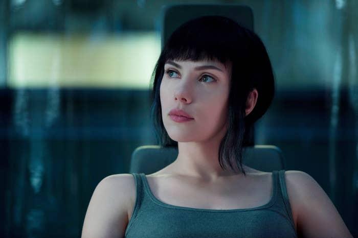 Scarlett Johansson as Motoko Kusanagi sitting in a chair and looking at something offscreen.