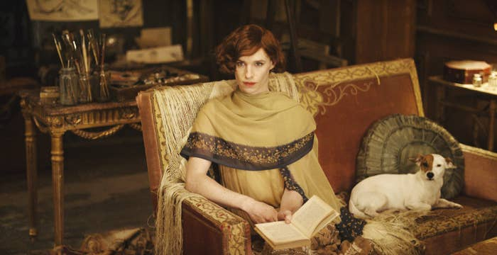 Eddie Redmayne as Lili Elbe, reading in a dress on her couch next to her dog.