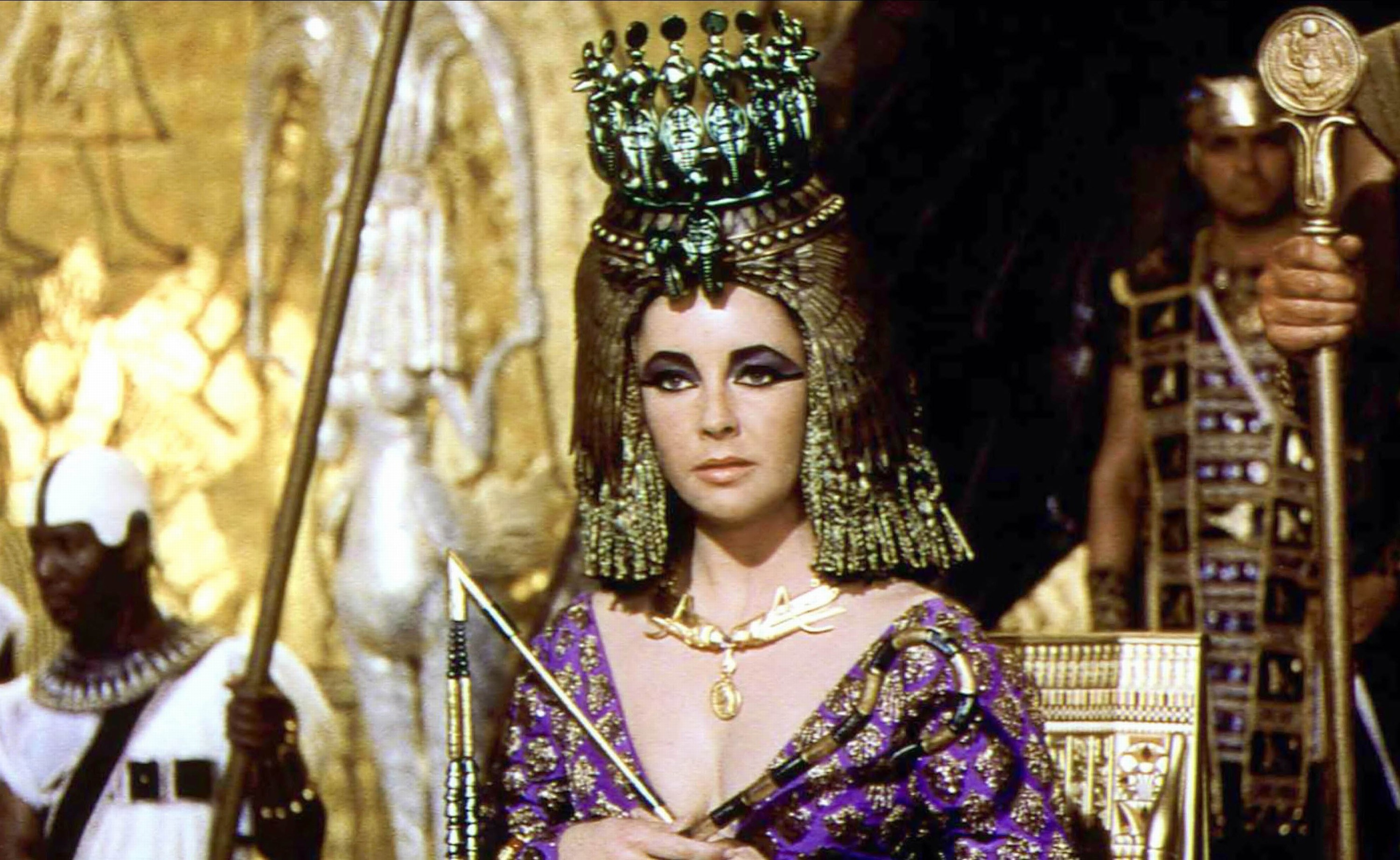 Elizabeth Taylor as Cleopatra, dressed in jewel-toned garbs and a gold headdress.