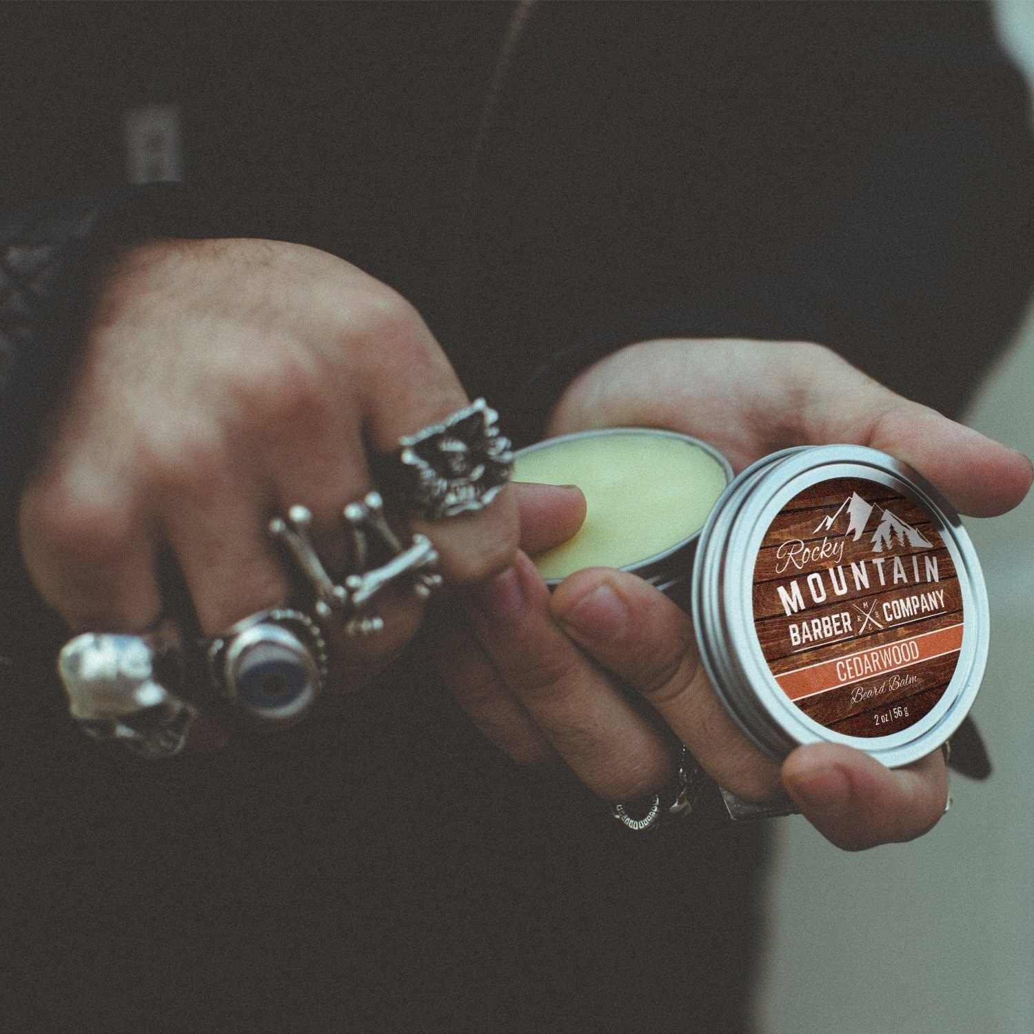 A close up of a person rubbing their thumb in the beard balm