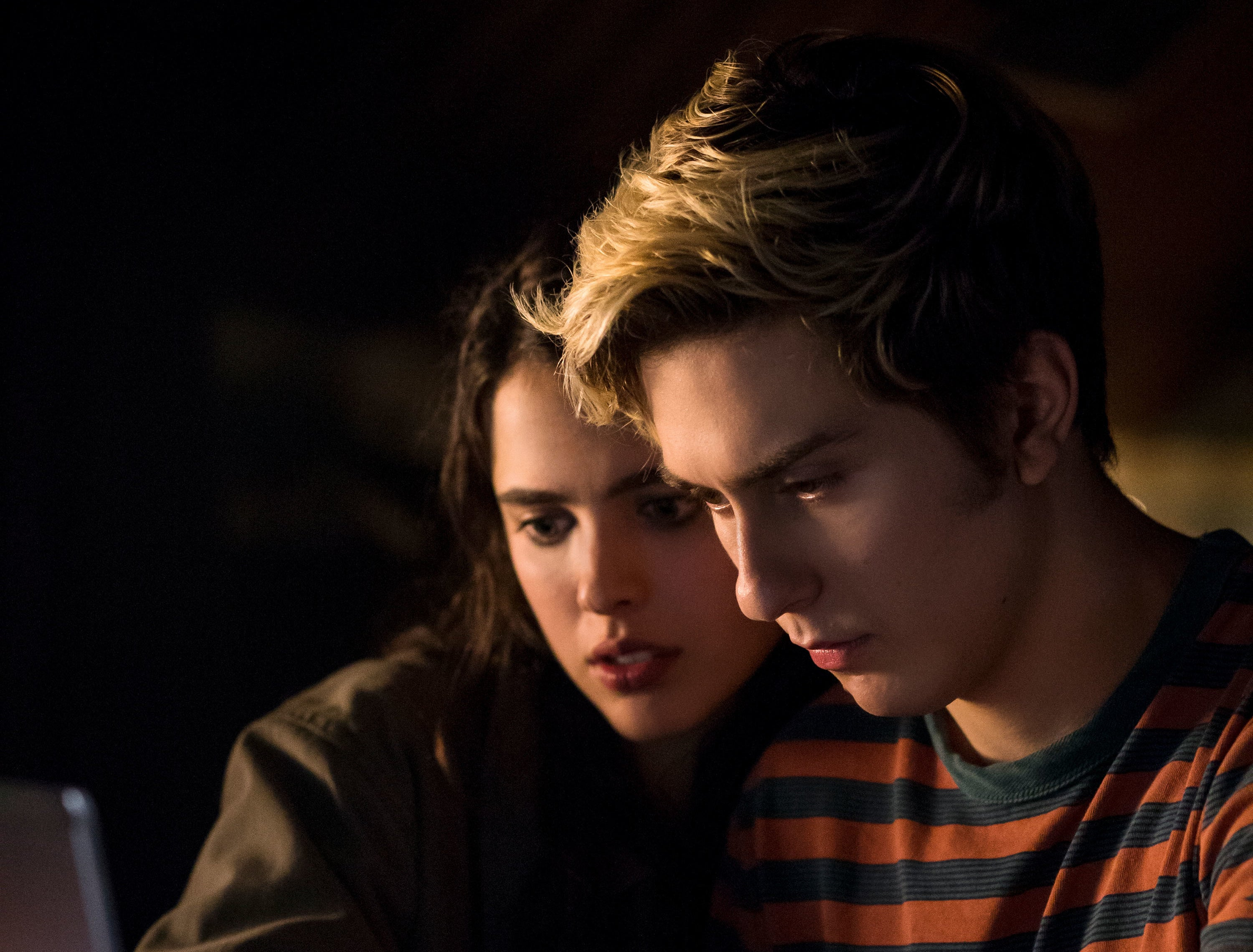 Nat Wolff as Light looking at content on his computer with his girlfriend.
