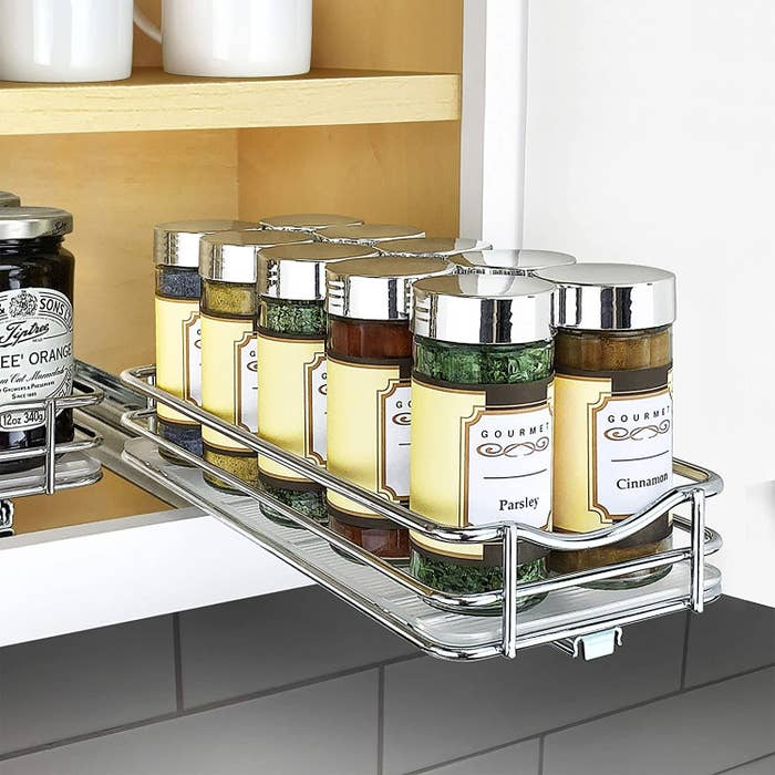 A metal rack of spices installed in a cabinet that pulls out (holding eight spice bottles)